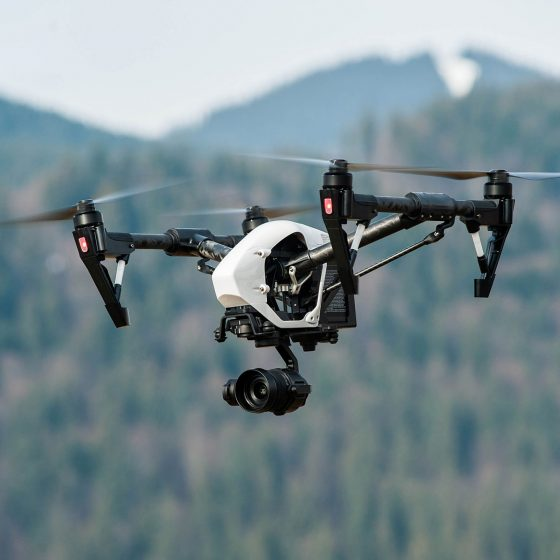Photo of a big drone with professional camera doing aerial videography and photography